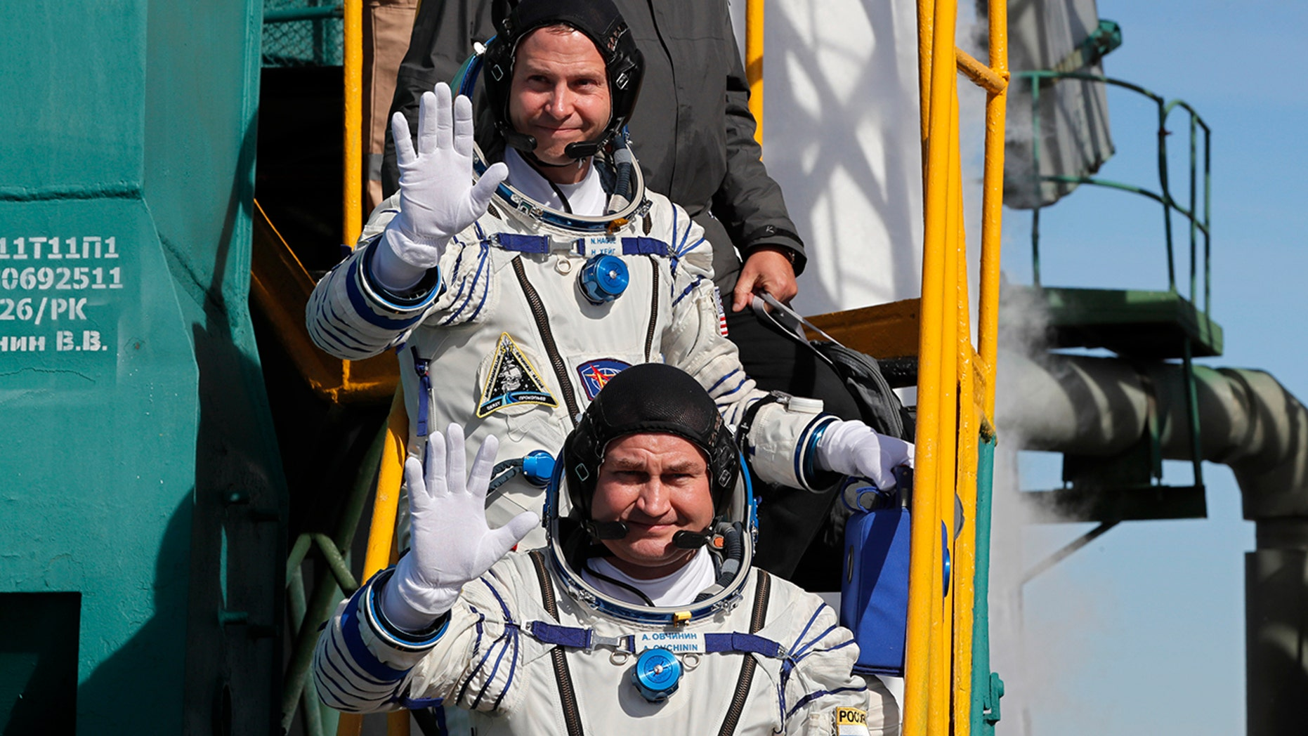U.S. astronaut Nick Hague right and Russian cosmonaut Alexey Ovchinin crew members of the mission to the International Space Station wave as they board the rocket prior to the launch of Soyuz-FG rocket at the Russian leased Baikonur cosmodrome Kazakhs