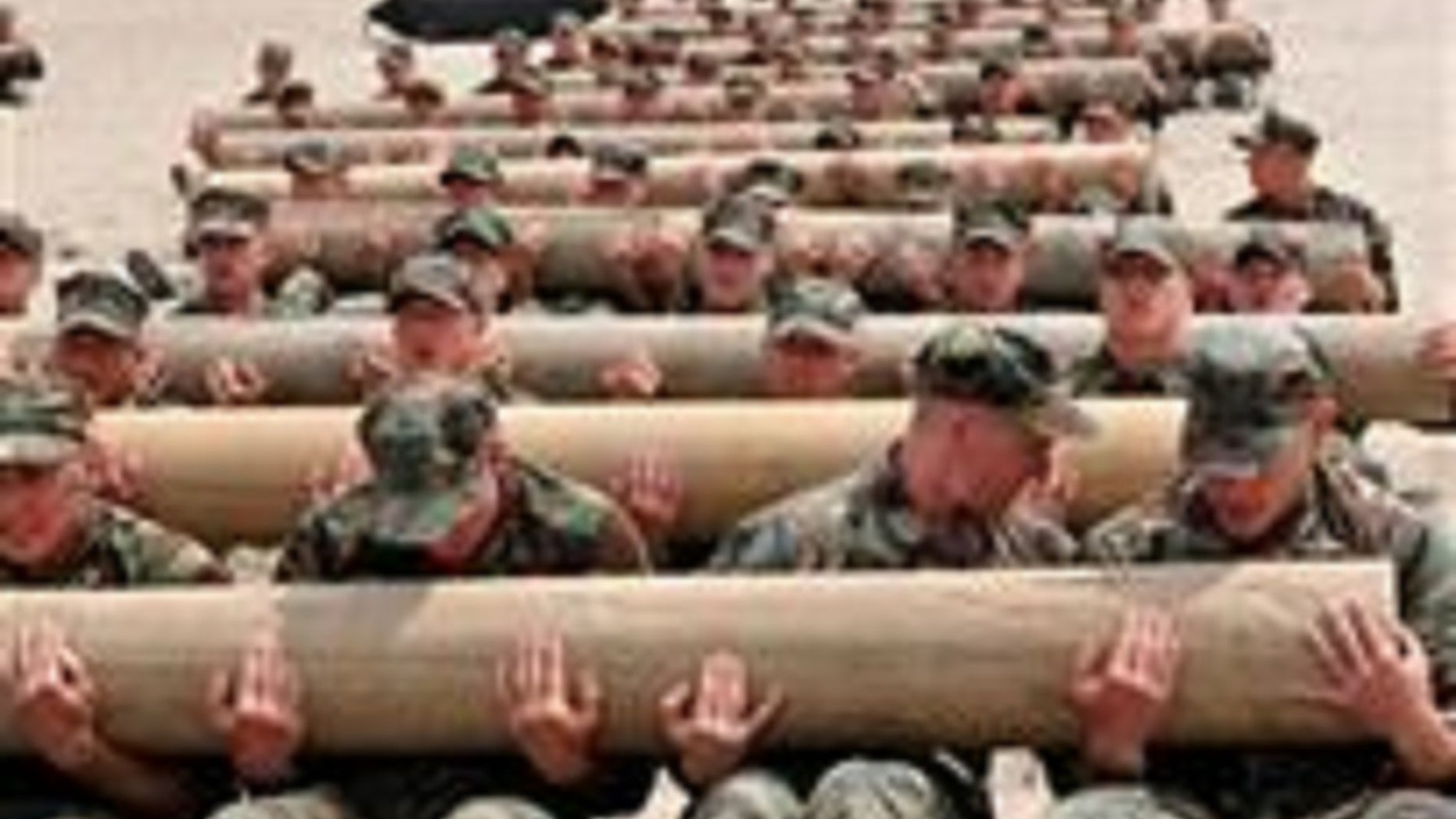 U.S. Navy SEAL candidates use teamwork to perform physical training exercises with 600-pound logs.