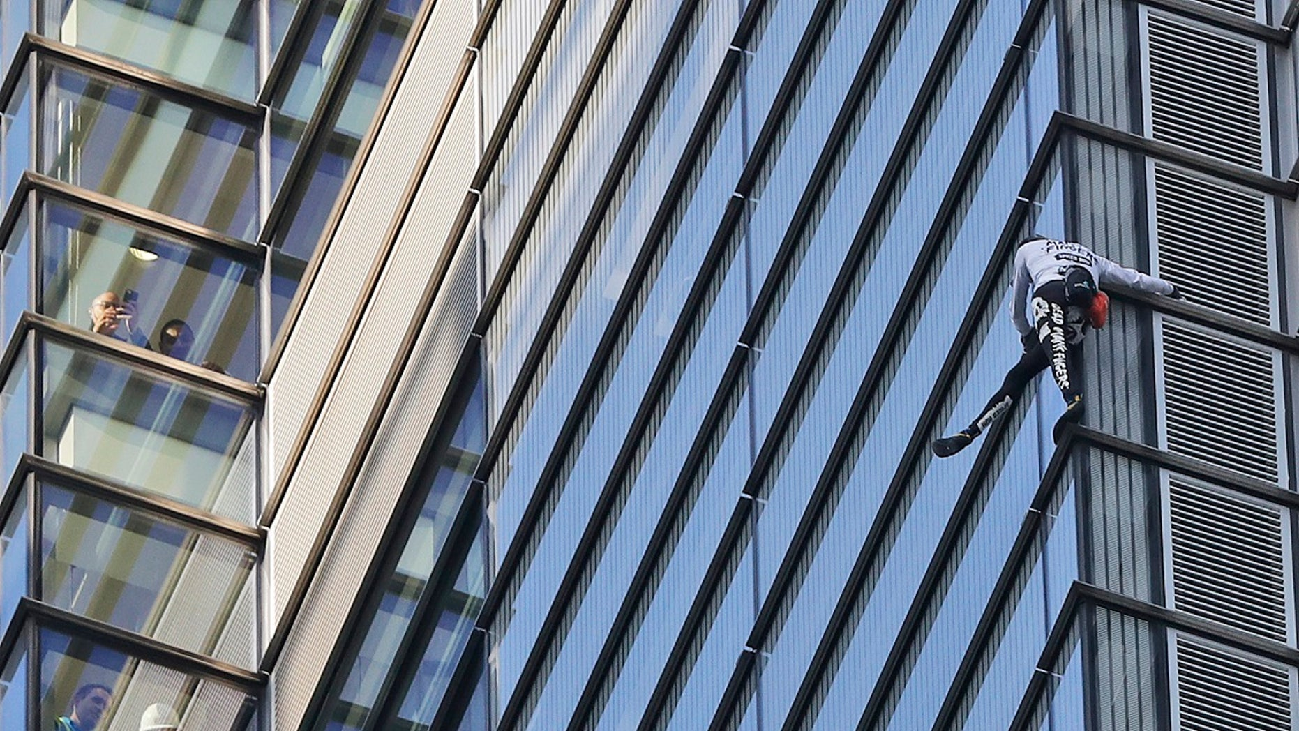 People watch from inside the building as urban climber dubbed the French Spider-Man, Alain Robert scales the outside of Heron Tower building in London