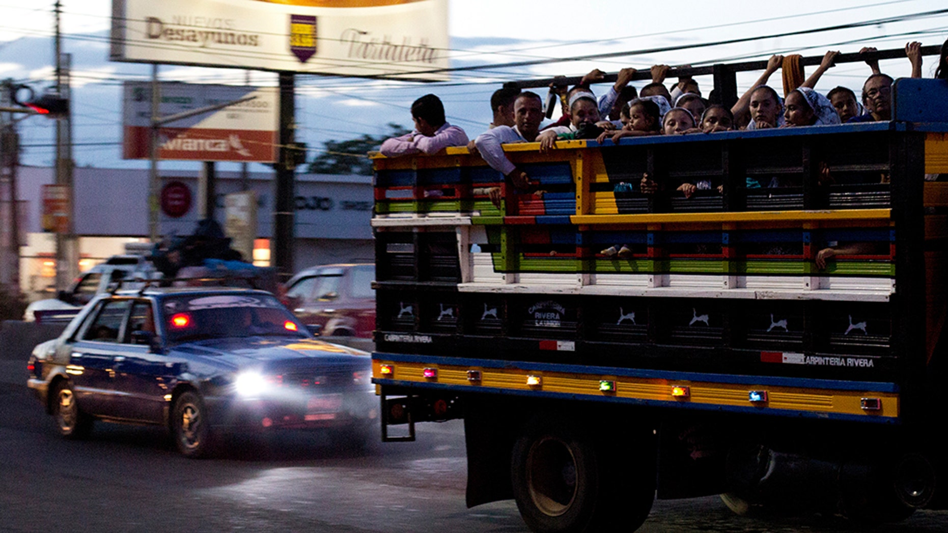 Commuters ride in the back of a pickup as night falls in San Miguel, El Salvador. It's a small country both geographically and by population, home to 6.5 million inhabitants. The International Organization for Migration estimates that another 1.35 million Salvadorans live in the United States. (AP Photo/Rebecca Blackwell, File)