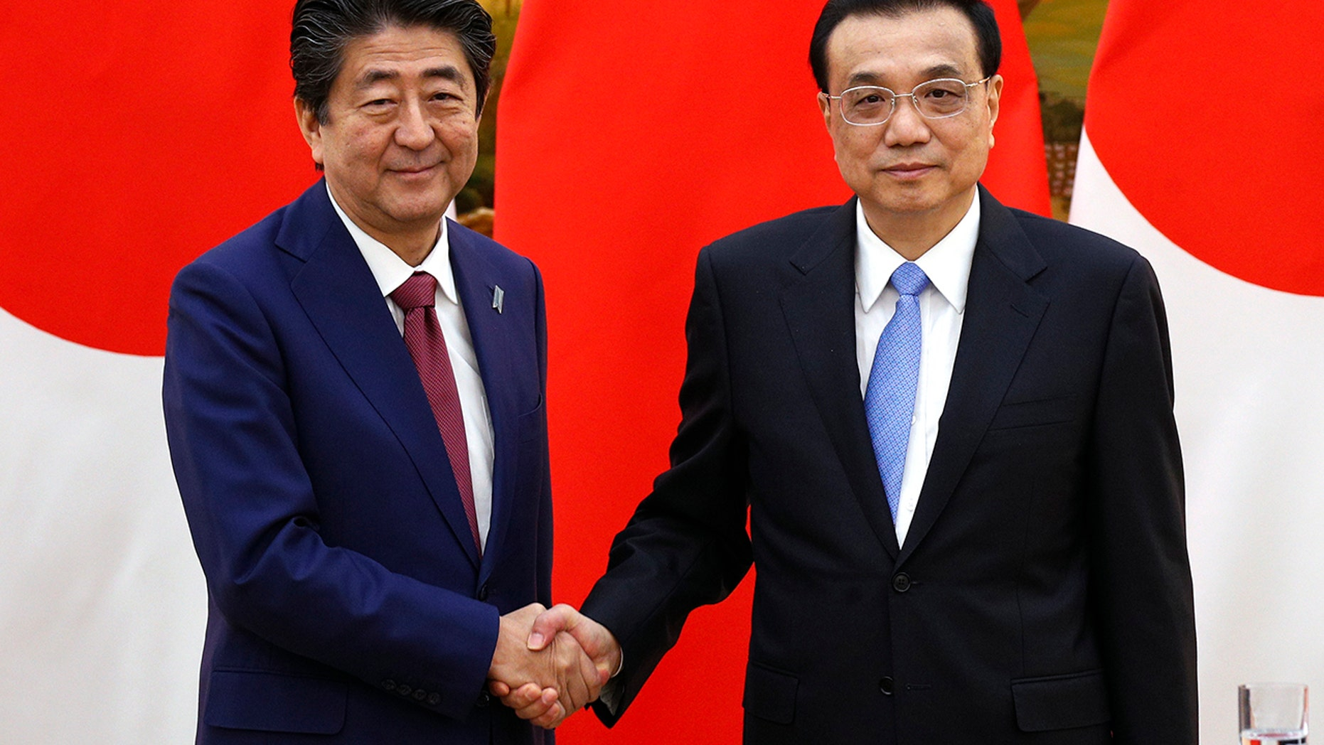 Japanese Prime Minister Shinzo Abe, left, shakes hands with Chinese Premier Li Keqiang after their joint news conference at the Great Hall of the People in Beijing, Friday, Oct. 26, 2018. (Associated Press)