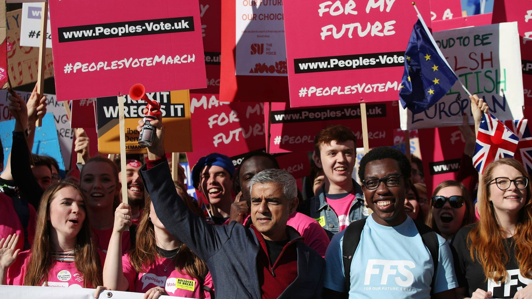 Mayor of London Sadiq Khan, front center, holds a klaxon horn, as he joins protesters in the People's Vote March for the Future, in London, Saturday Oct. 20, 2018. Some thousands of protesters are marching through central London, Saturday, to demand a new referendum on Britain's Brexit departure from the European Union.