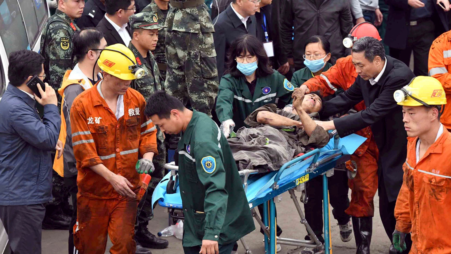 In this photo released by China's Xinhua News Agency, a worker is carried on a stretcher out of the Longyun coal mine in Yuncheng County, east China's Shandong Province, Sunday, Oct. 21, 2018.
