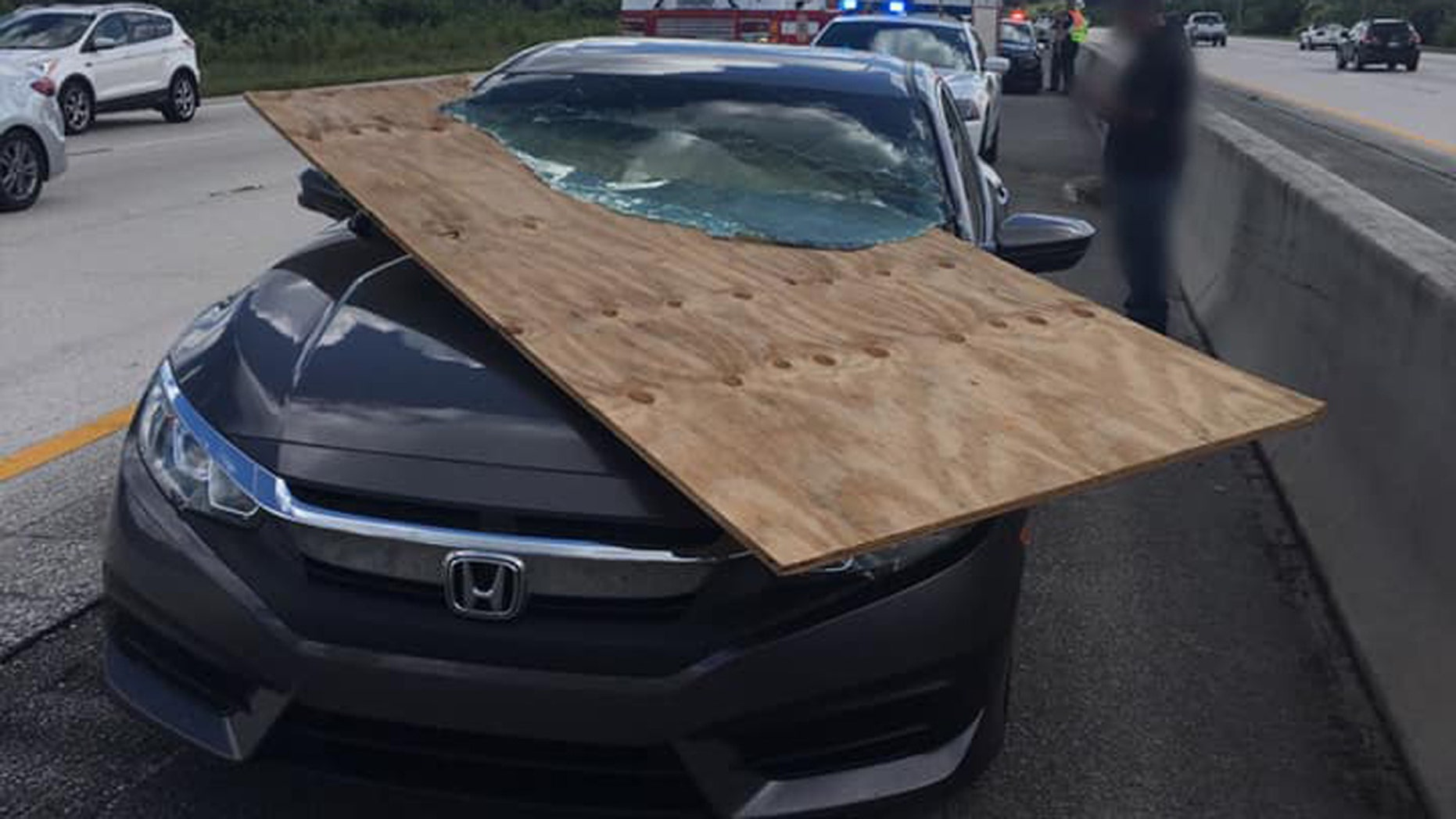 A motorist in Florida had a near-miss after a piece of plywood flew off a truck and became impaled in her windshield.