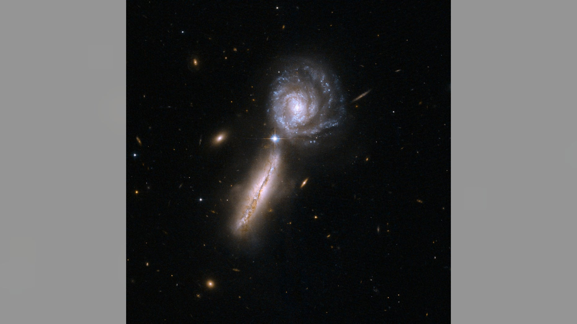The spiral galaxies UGC 9618 and VV 340, which are about to collide. Astronomers believe such galaxy mergers also usually involve the merger of the supermassive black holes at galaxies' cores.