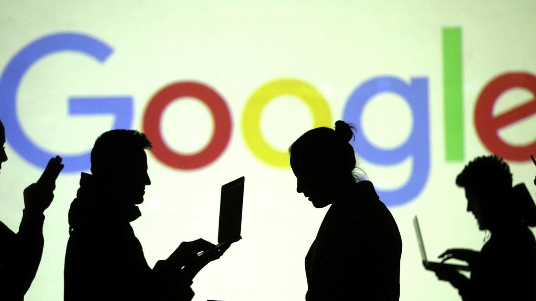Silhouettes of laptop and mobile device users are seen next to a screen projection of Google logo in this picture illustration taken March 28, 2018. (REUTERS/Dado Ruvic/Illustration)