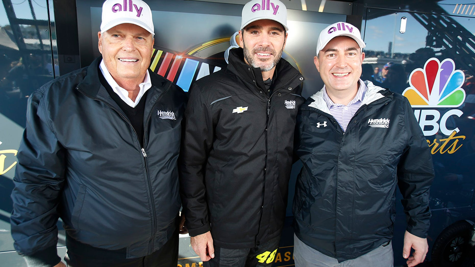 Jimmie Johnson, center, poses with owner Rick Hendrick, left, and Ally Financial CEO Jeffery Brown, right.