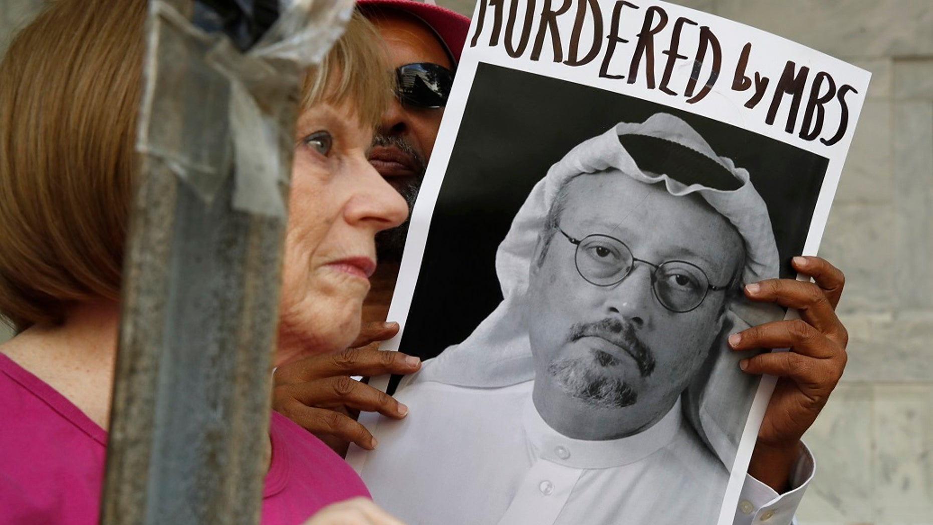 FILE - People hold signs during a protest at the Embassy of Saudi Arabia about the disappearance of Saudi journalist Jamal Khashoggi. in Washington.