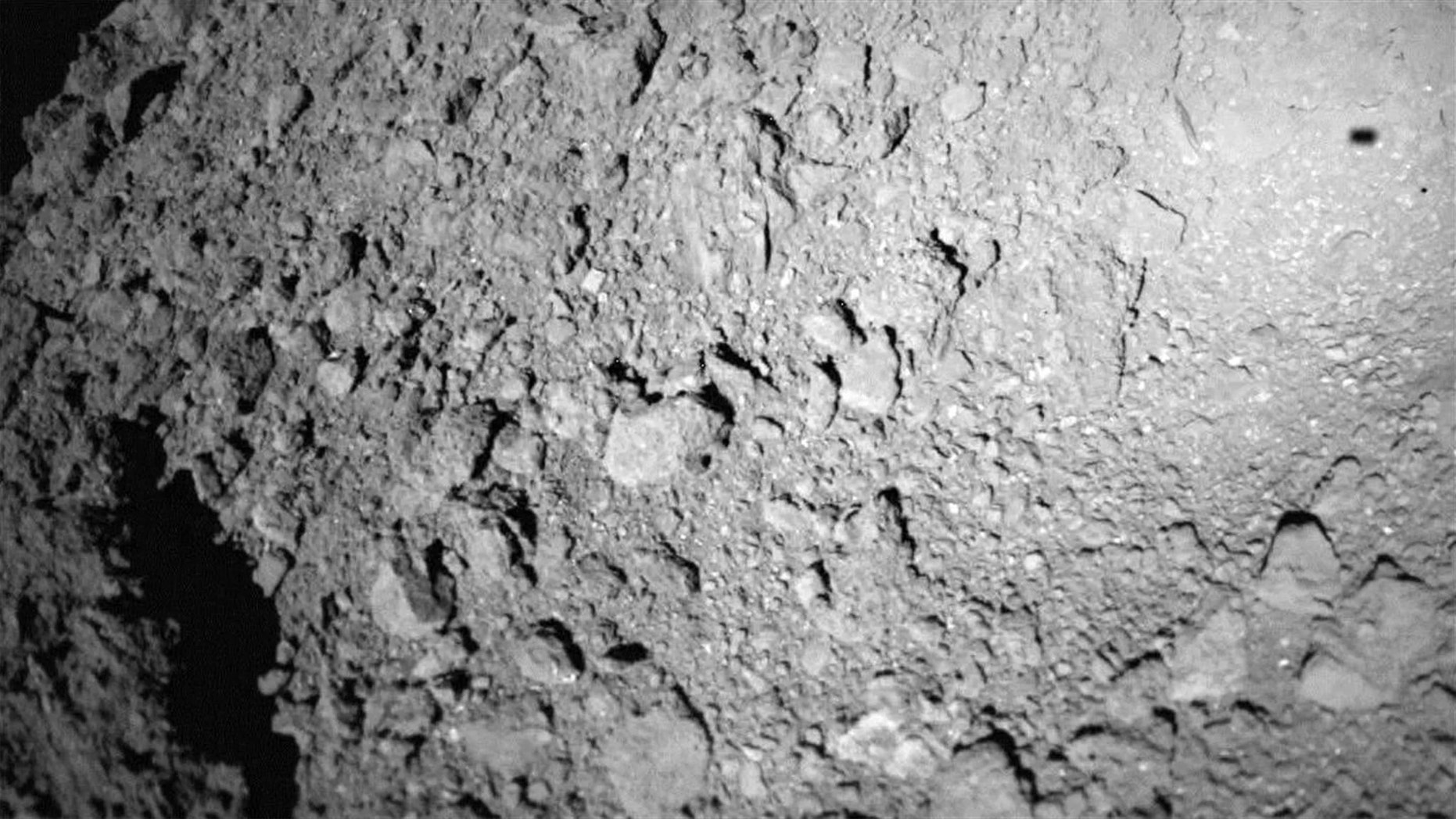 The German-French Mobile Asteroid Surface Scout (MASCOT) lander captured this photo of asteroid Ryugu during landing operations on Oct. 3, 2018. The lander's shadow is visible at upper right. Credit: German Aerospace Center (DLR)