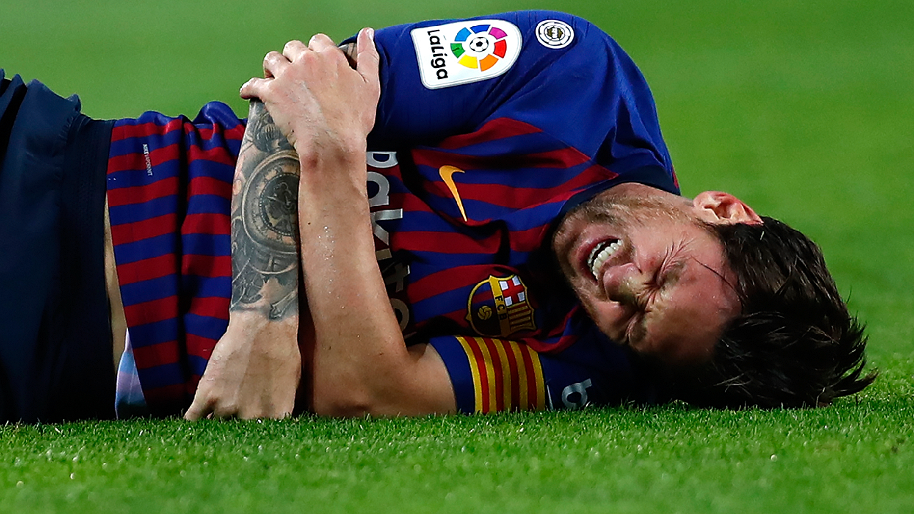 FC Barcelona's Lionel Messi looks painfully injured during the Spanish La Liga soccer match between FC Barcelona and Sevilla at the Camp Nou stadium in Barcelona, Spain, Saturday, Oct. 20, 2018.