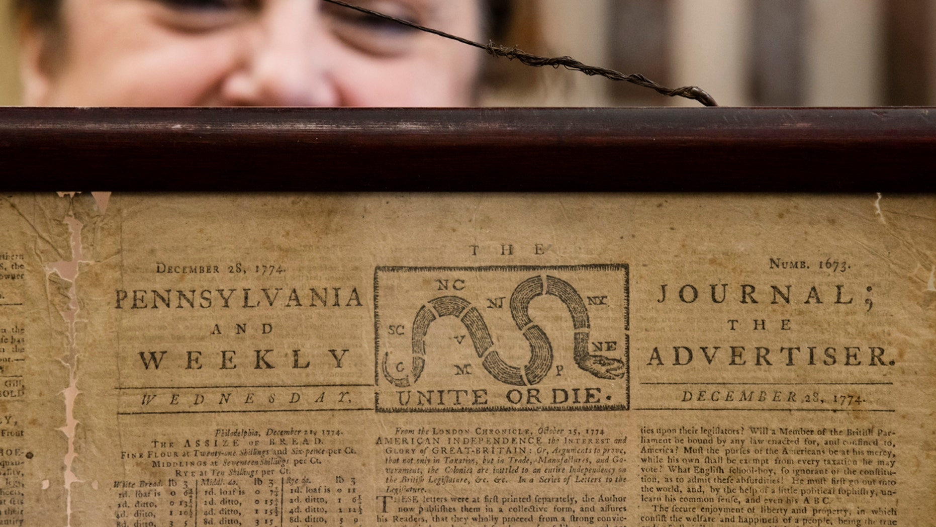 Heather Randall displays a Dec. 28, 1774, Pennsylvania Journal and the Weekly Advertiser at the Goodwill Industries in Bellmawr, N.J., Thursday.