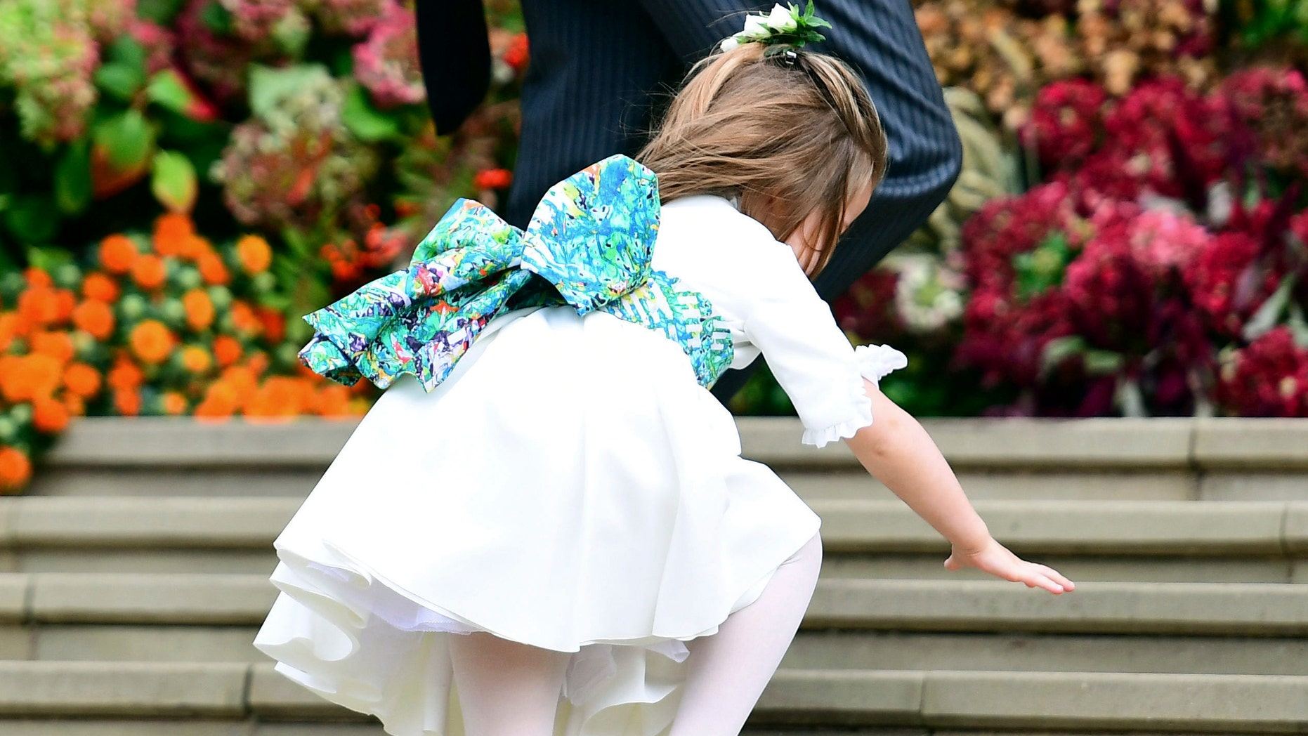 Britain's Princess Charlotte falls on the steps, as the bridesmaids and page boys arrive for the wedding of Princess Eugenie of York and Jack Brooksbank at St George's Chapel. (AP)