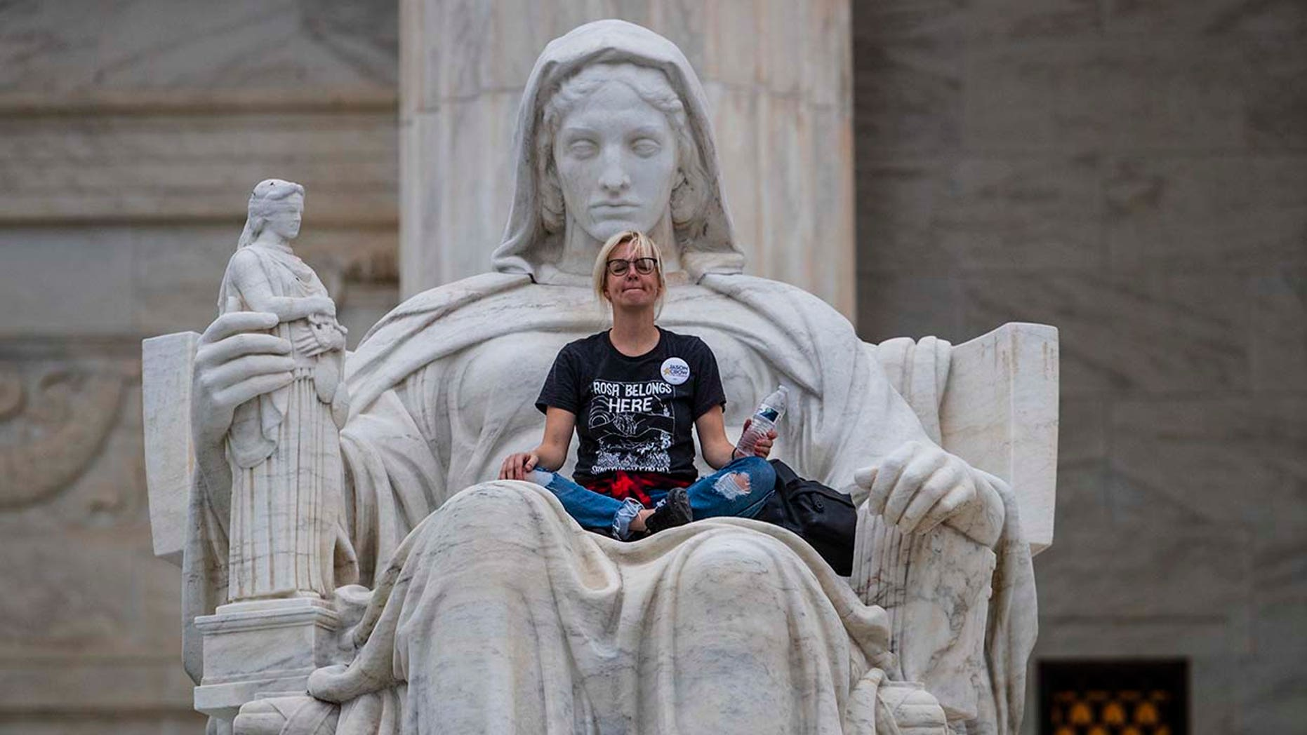 Jessica Campbell-Swanson, an activist from Denver, sits in the lap of a sculpture known as the Statue of Contemplation of Justice on the steps of the Supreme Court Building where she and others protested the confirmation of Brett Kavanaugh as the high court's newest justice, in Washington, Saturday, Oct. 6, 2018. (AP Photo/J. Scott Applewhite)