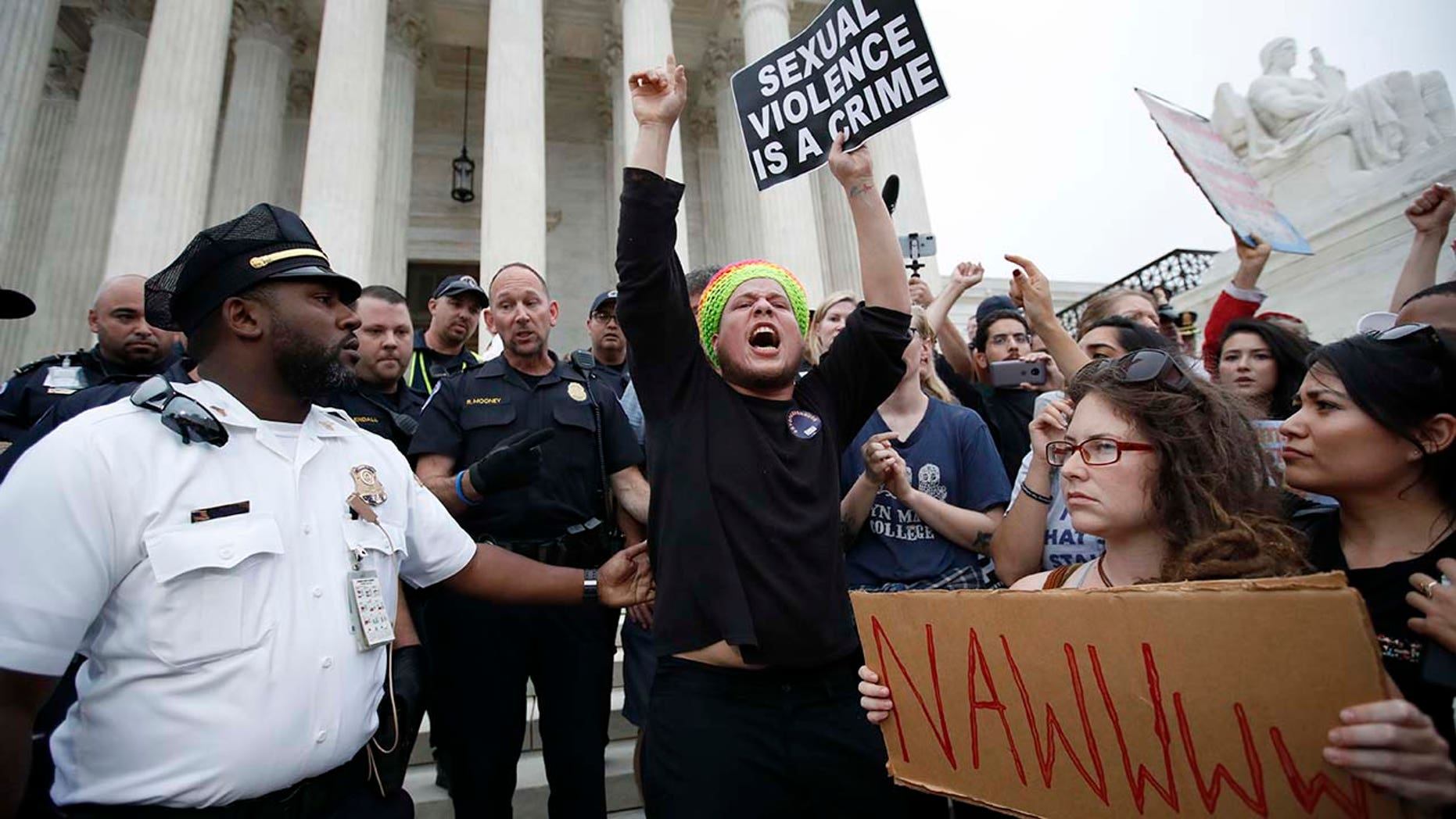 Police move activists as they protest on the steps of the Supreme Court after the confirmation vote of Supreme Court nominee Brett Kavanaugh, on Capitol Hill, Saturday, Oct. 6, 2018 in Washington. (AP Photo/Alex Brandon)