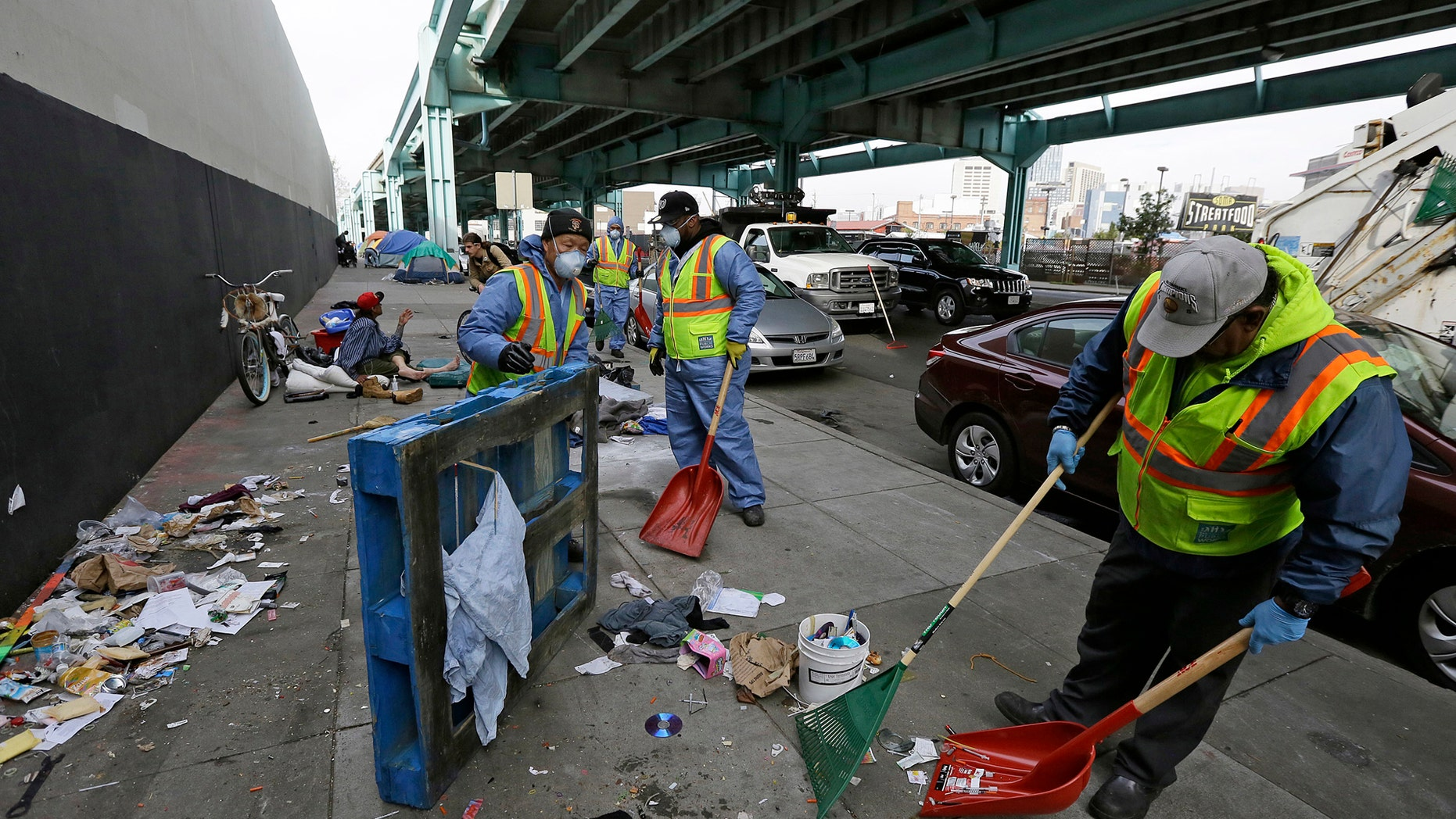 FILE - In this Feb. 26, 2016 file photo, city workers clear away debris that includes syringes from the remains of a tent city along Division Street in San Francisco. Sean Miller, a 24-year-old transplant, is offering a free app to make it easier for people to report waste - human and otherwise - and used needles and anything else gross on the famously dirty streets of San Francisco. (AP Photo/Eric Risberg, File)
