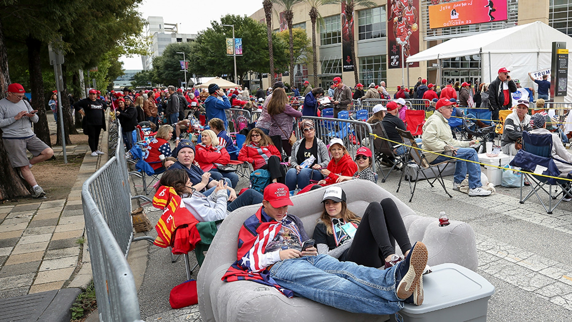 Kersten Buck, 25, and her fiance Clayton Dupree, 25, sit on an inflatable couch as they wait for a President Trump rally for Sen. Ted Cruz at the Toyota Center on Monday in Houston. (Godofredo A. Vasquez/Houston Chronicle via AP)