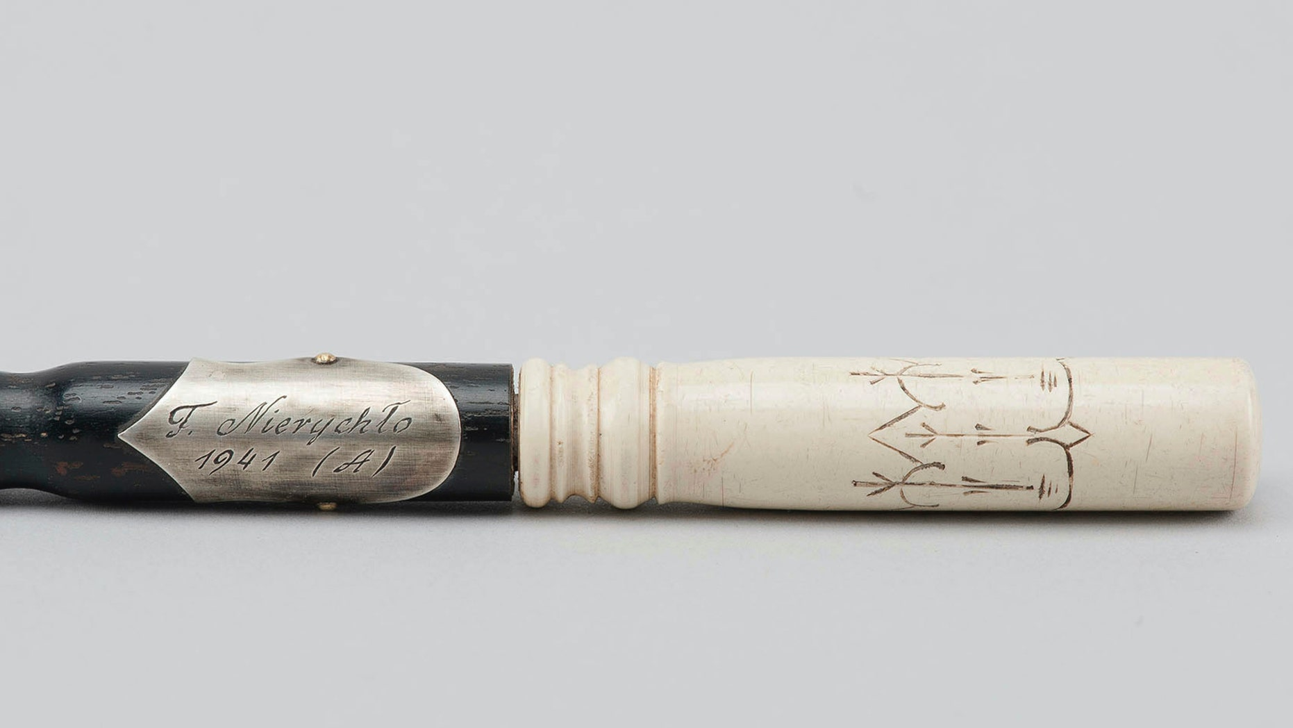 In this Oct. 24, 2018 photo publicly provided by the Museum of the former Nazi German death camp of Auschwitz Birkenau is seen the wood-and-ivory baton of Franciszek Nierychlo, Auschwitz prisoner and controversial organizer and first conductor of the inmates' orchestra, in Oswiecim, Poland. (Museum of the former Nazi German death camp of Auschwitz Birkenau/Marcin Inglot via AP)