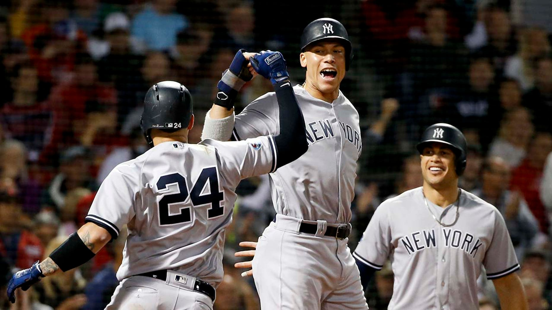 New York Yankees' Gary Sanchez, left, celebrates after his three-run home run against the Boston Red Sox with Aaron Judge and Giancarlo Stanton during the seventh inning of Game 2 of a baseball American League Division Series, Saturday, Oct. 6, 2018, in Boston. (Associated Press)