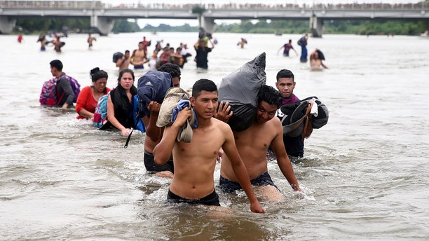 Central American migrants, part of a caravan trying to reach the U.S., cross the Suchiate River to avoid the border checkpoint in Ciudad Hidalgo, Mexico, October 20, 2018. REUTERS/Edgard Garrido