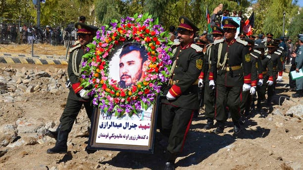 Guards of honor carry a photo of Gen. Abdul Raziq, Kandahar police chief, who was killed by a guard, during his burial ceremony in Kandahar, Afghanistan, Friday, Oct. 19, 2018.
