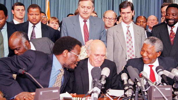 FILE - This April 19, 1994 file photo shows in the front row; Inkatha Freedom Party (IFP) Chief Mangosuthu Buthelezi, left, President F.W. de Klerk, middle, and African National Congress (ANC) President Nelson Mandela, right, exchanging words at a news conference, while in the back row at center South African Foreign Minister Pik Botha looks over them, in Pretoria, South Africa. Botha, the last foreign minister of South Africa's apartheid era and a contradictory figure who staunchly defended white minority rule but eventually recognized that change was inevitable, died on Friday, Oct. 12, 2018 at age 86. Next to Botha, second from right is Roelf Meyer, chief government negotiator, and ANC's Secretary General Cyril Ramaphosa, right. (AP Photo/Lynne Sladky, File)