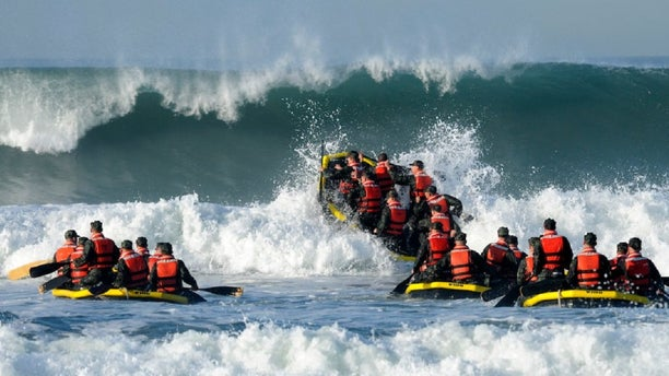 """Students participate in the Navy Basic Underwater Demolition course during an evolution, which is part of Navy SEAL training, known as """"surf passage"""" on Amphibious Base Coronado, Calif."""