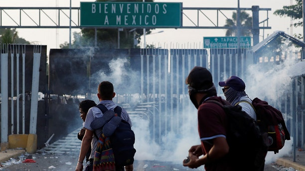 Men throw stones to the Mexican Police after they pull down the border gate with the intention to carry on their journey in Tecun Uman, Guatemala.