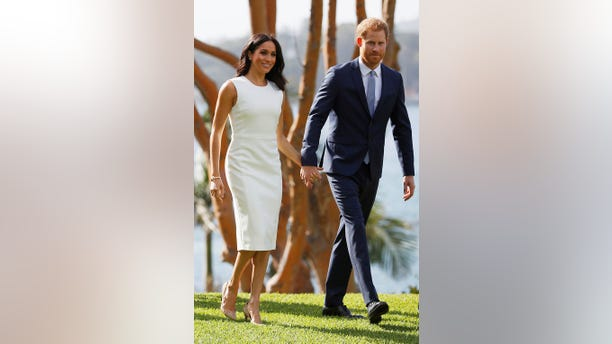 Prince Harry and Meghan Markle hold hands as they visit the Admiralty House in Sydney, Australia, on Oct. 16, 2018.