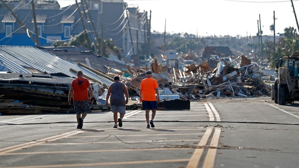 People walk amidst destruction on the main street of Mexico Beach, Fla.