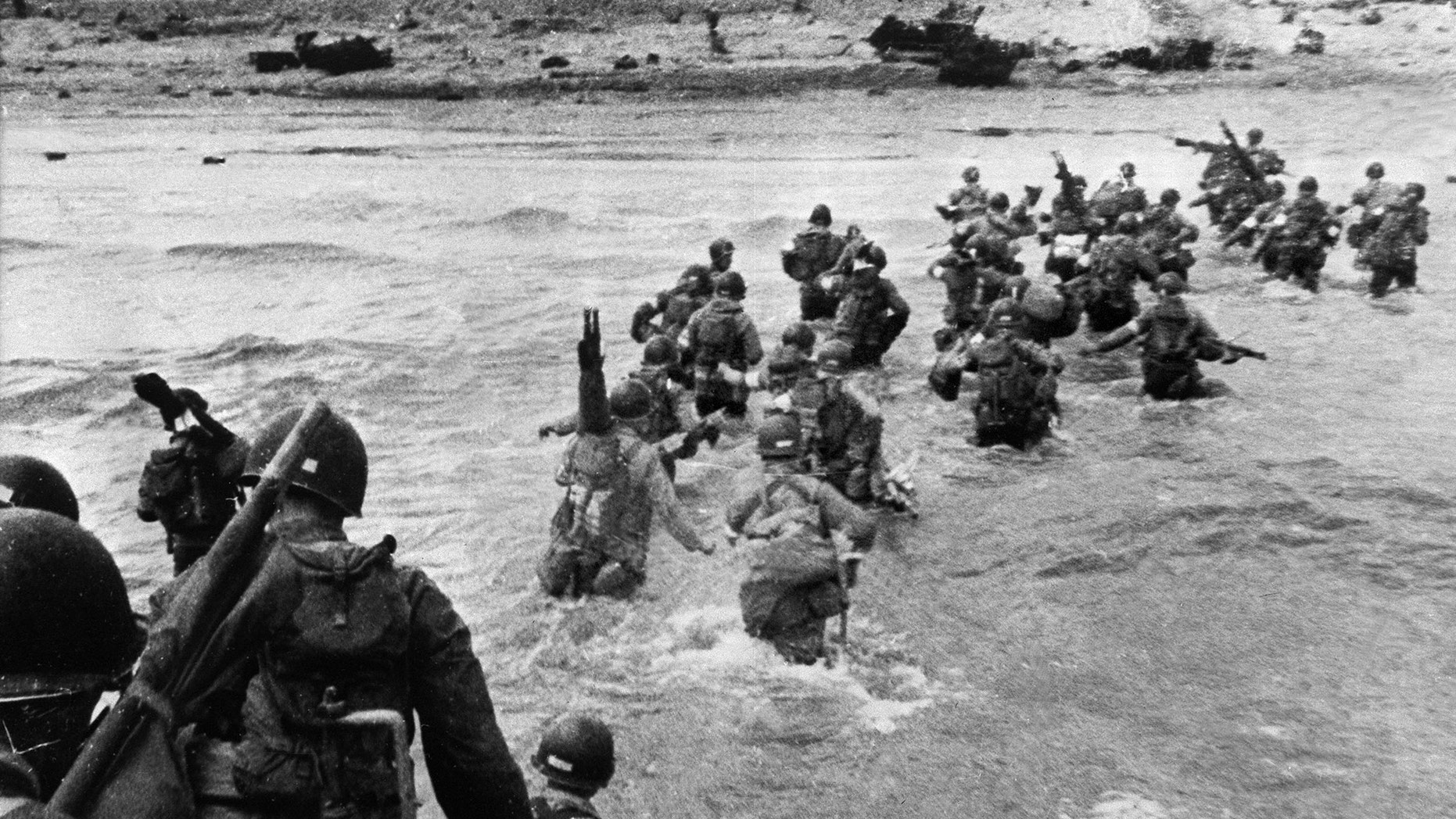 File photo - American troops supporting those already on the coast of Northern France, plunge into the surf and wade shoreward carrying equipment, on Utah Beach, Les Dunes de Madeleine, France.