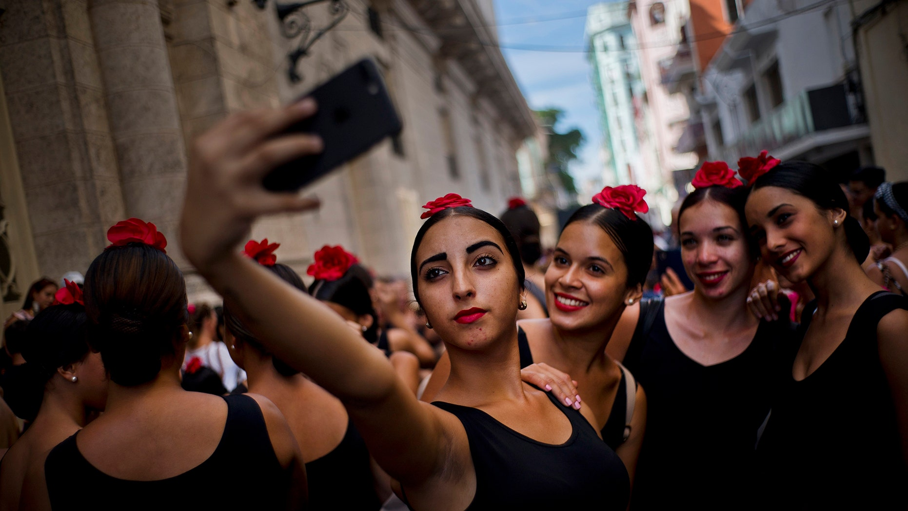 Young flamenco dancers take a selfie before performing in the street during the 26th International Ballet Festival in Havana, Cuba, Sunday, Nov. 4, 2018. (Associated Press)