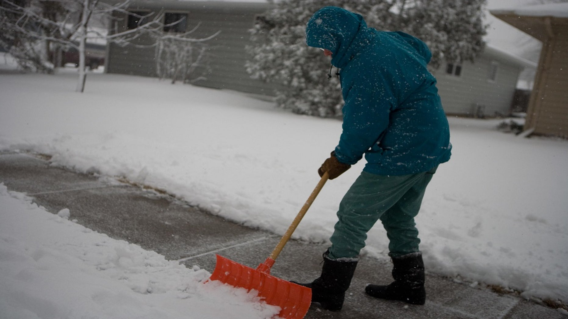 FILE: A resident digs out snow on the sidewalks in Fargo, North Dakota. A Minneapolis city official who supported a tougher approach on residents shoveling sidewalks was issued a fine herself.