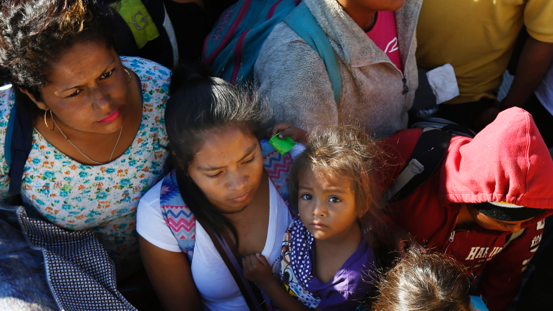 Migrants traveling with a caravan hoping to reach the U.S. border, wait to board a bus in La Concha, Mexico, Wednesday, Nov. 14, 2018. Buses and trucks are carrying some migrants into the state of Sinaloa along the Gulf of California and further northward into the border state of Sonora. The bulk of the main caravan appeared to be about 1,100 miles from the border, but was moving hundreds of miles per day. (AP Photo/Marco Ugarte)
