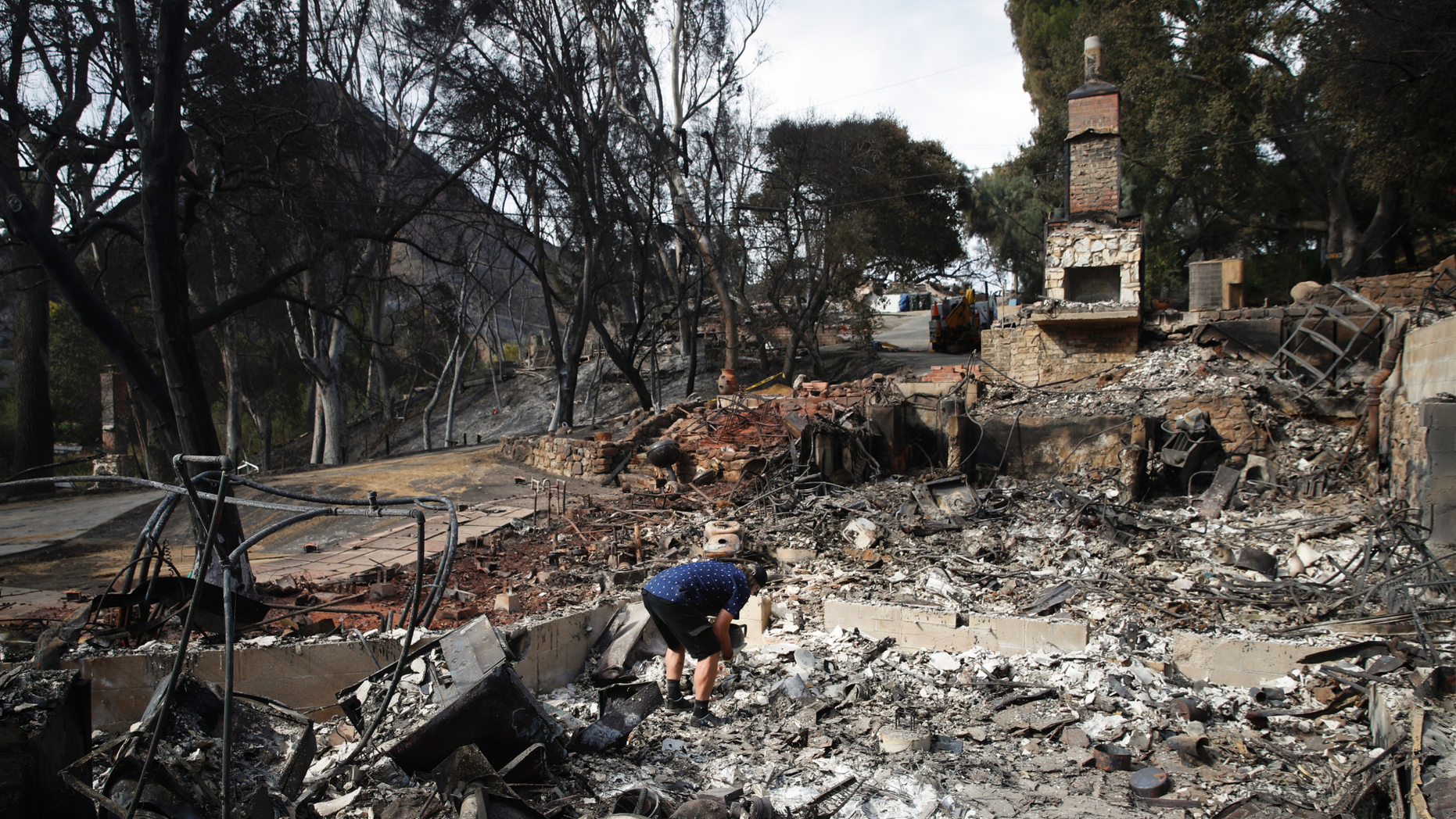 Roger Kelton searches through the remains of his mother-in-law's home leveled by the Woolsey Fire, Tuesday, Nov. 13, 2018, in the southern California city of Agoura Hills. (AP Photo/Jae C. Hong)