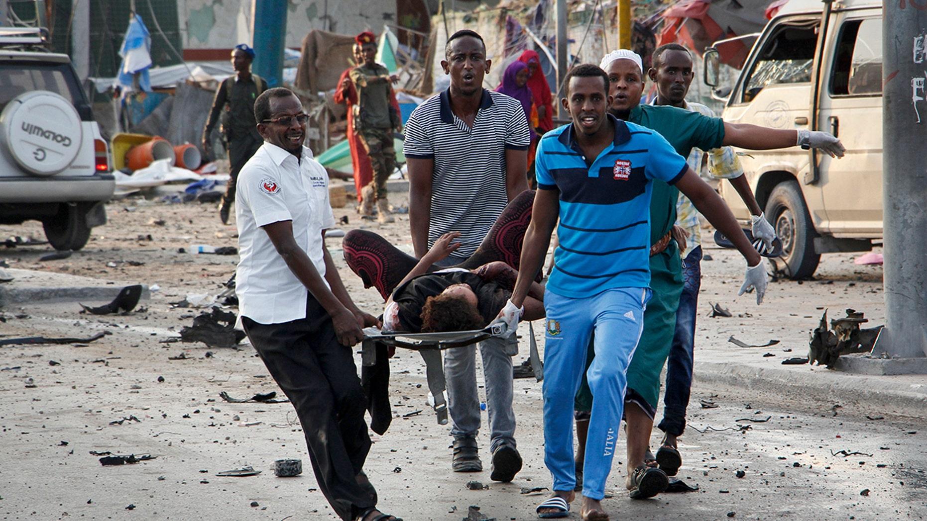 Somalis carry away an injured civilian who was wounded in a bomb blast near the Sahafi hotel in the capital Mogadishu, Somalia.