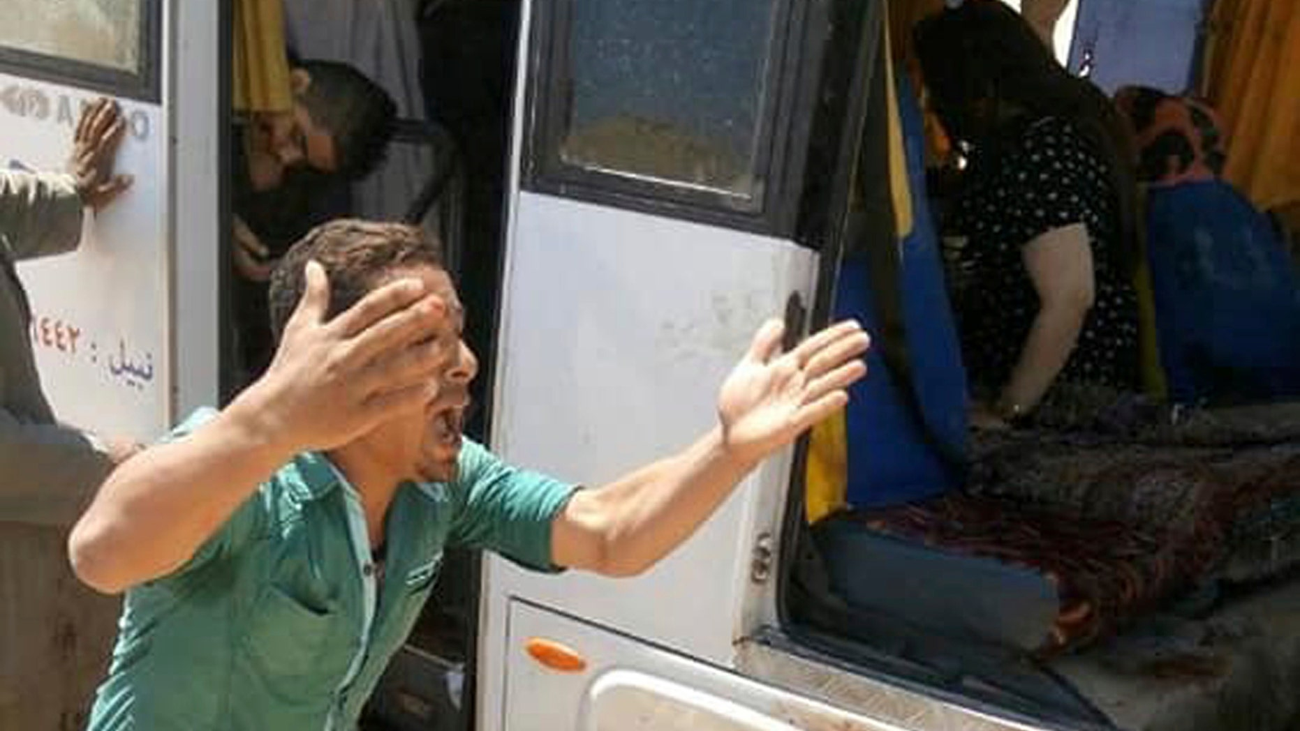 A man screams beside a bus carrying Coptic Christians which came under attack outside Cairo, Friday, Nov. 2, 2018. Islamic militants on Friday ambushed a bus carrying Christian pilgrims on their way to a remote desert monastery south of the Egyptian capital, killing at least seven and wounding a dozen more, the Interior Ministry said. (Egypt's Coptic Orthodox Church via AP)
