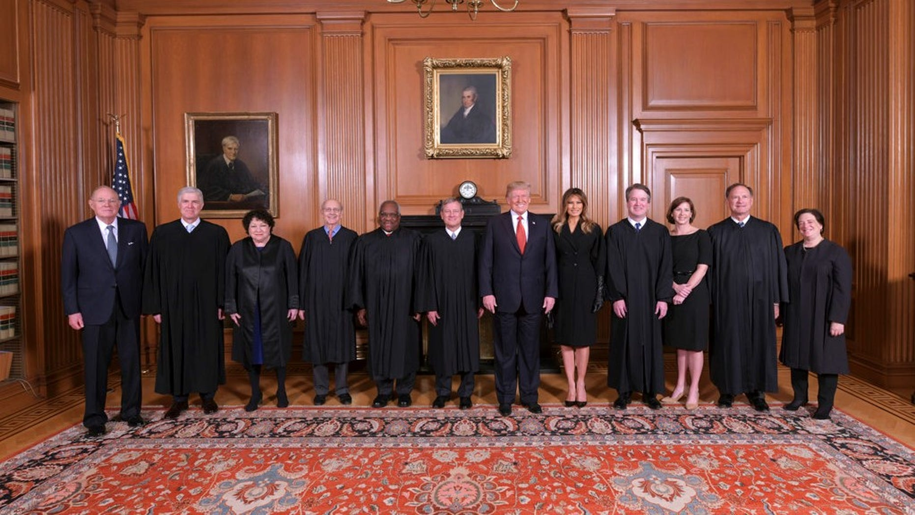 In this image provided by the Supreme Court, President Donald Trump poses for a photo with Associate Justice Brett Kavanaugh in the Justices' Conference Room before a investiture ceremony Thursday, Nov. 8, 2018, at the Supreme Court in Washington. From left are, retired Justice Anthony Kennedy, Associate Justices Neil Gorsuch, Sonia Sotomayor, Stephen Breyer, Clarence Thomas, Chief Justice John Roberts, Jr., President Donald Trump, first lady Melania Trump, Associate Justice Brett Kavanaugh, Ashley Kavanaugh, and Associate Justices Samuel Alito, Jr. and Elena Kagan.