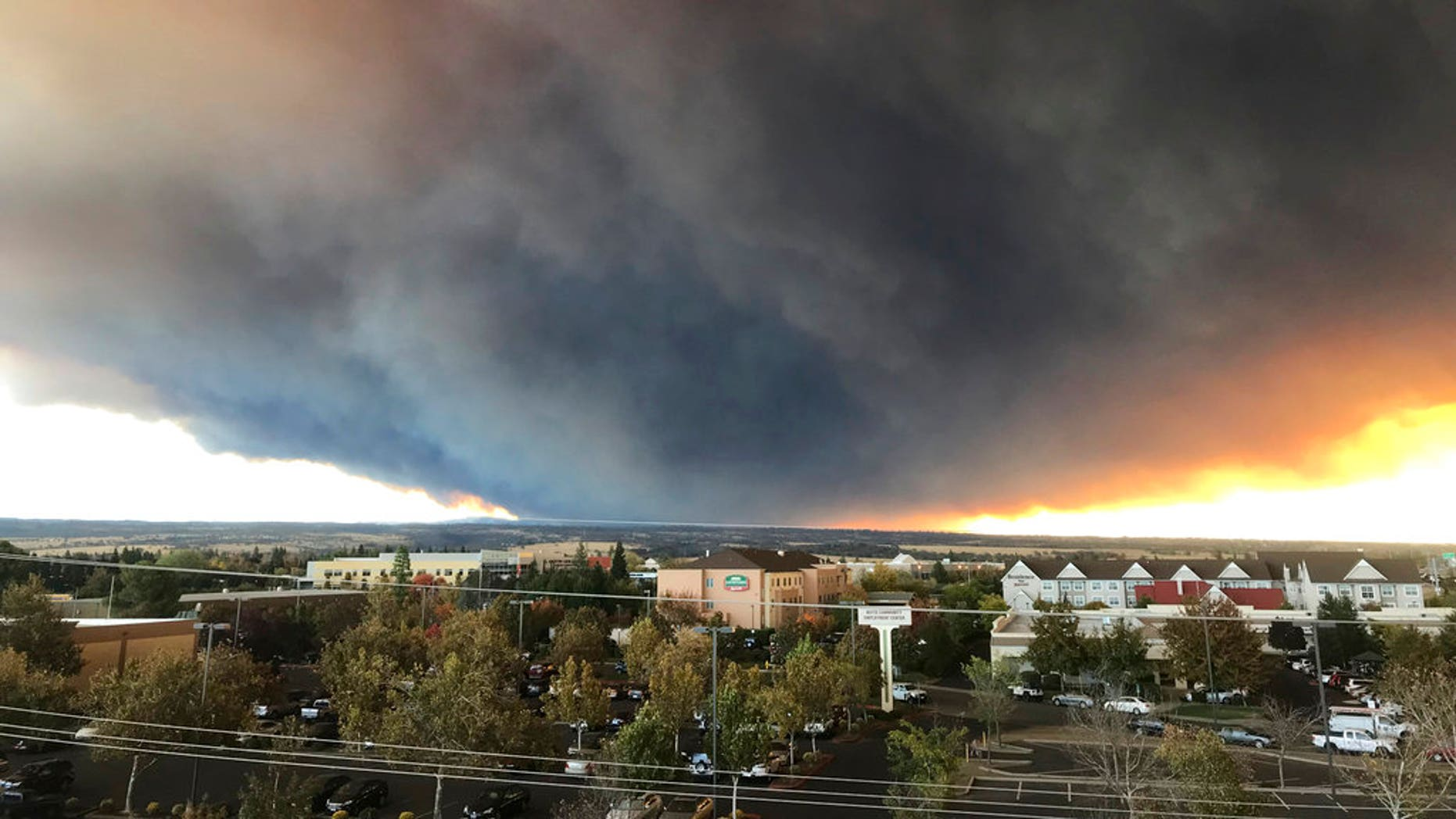 The massive plume from the Camp Fire, burning in the Feather River Canyon near Paradise, Calif., wafts over the Sacramento Valley as seen from Chico, Calif.