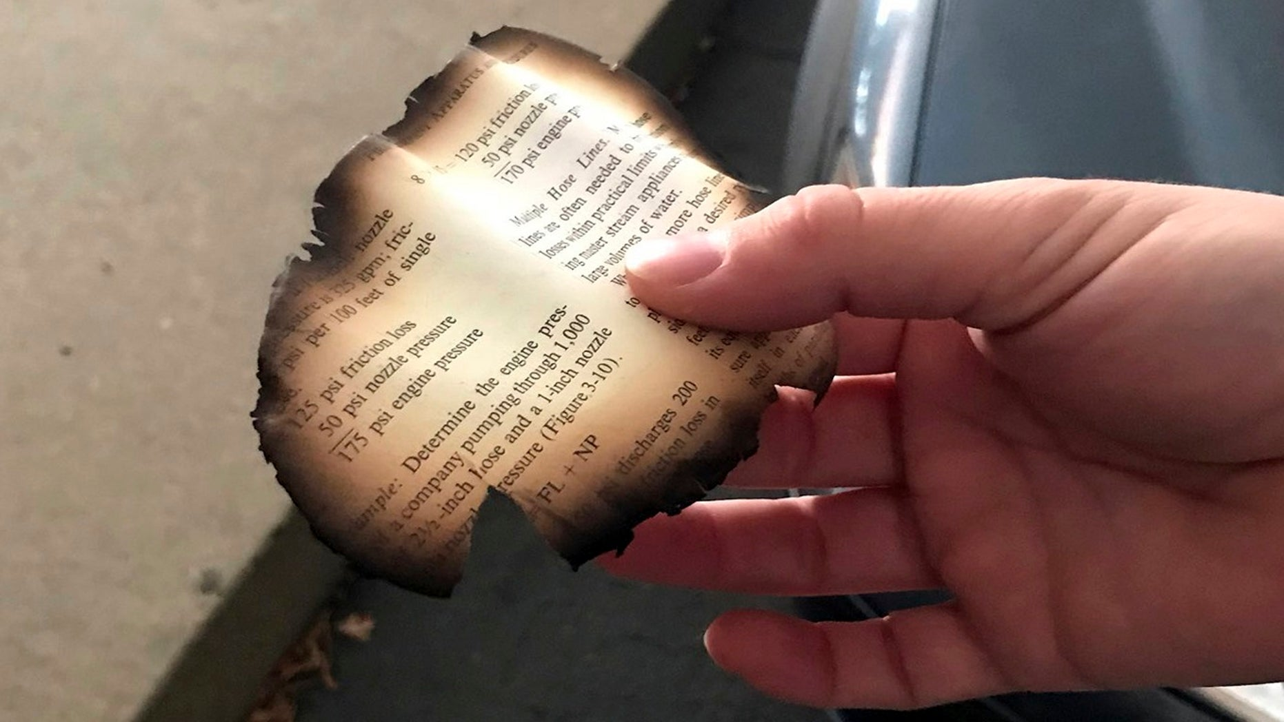 This photo provided by Nicole Kowalczyke shows a piece of a burned page that fell out of the sky in Chico, Calif., Thursday, Nov. 8, 2018, as the Camp Fire burns nearby.