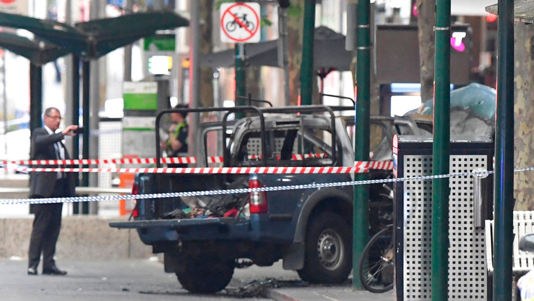 A burnt out vehicle is seen on Bourke Street in Melbourne, Friday, Nov. 9, 2018. A knife-wielding man stabbed two people, one fatally, in Australia's second-largest city last Friday in an attack likely linked to terrorism, police said.