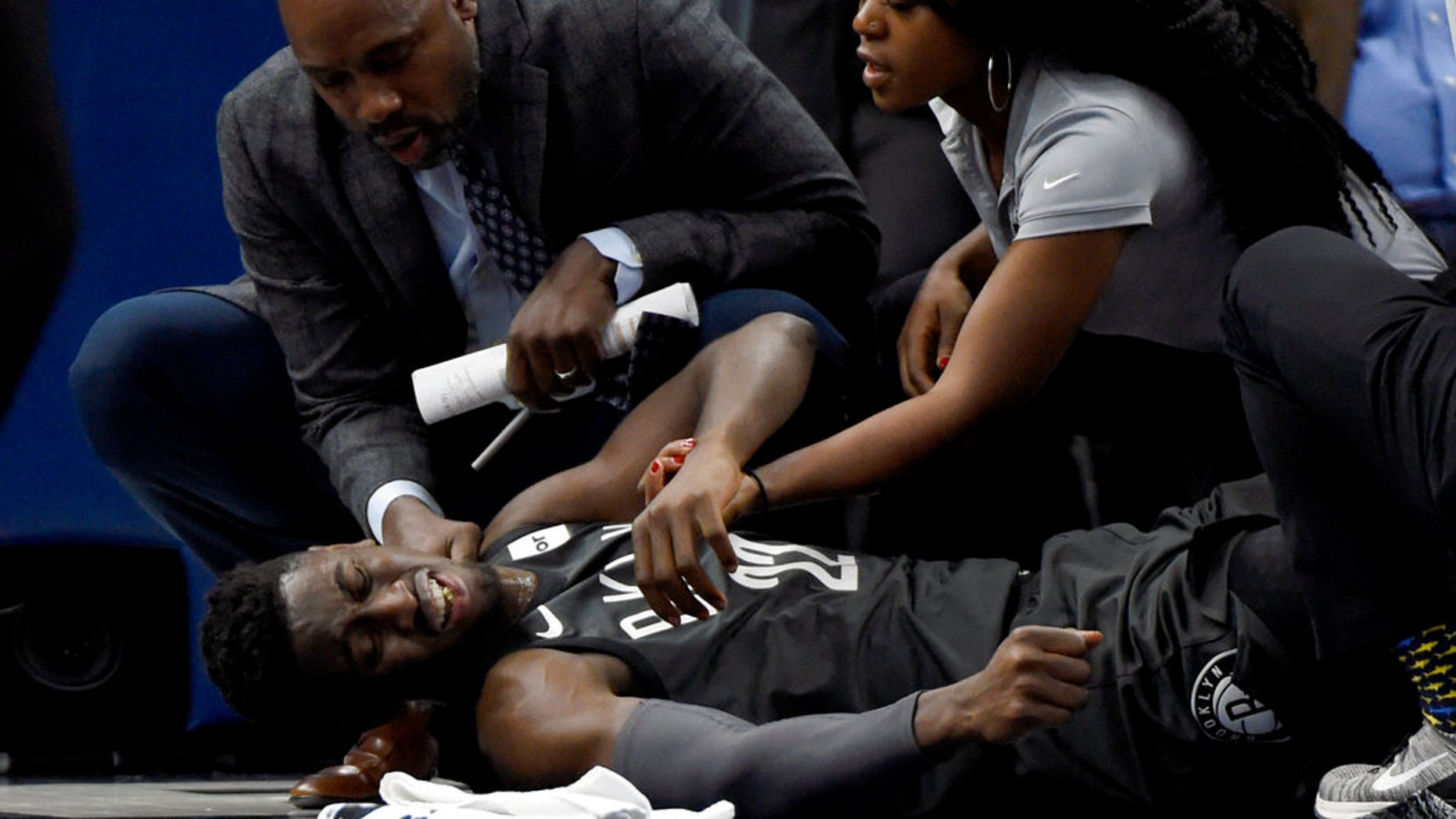 Brooklyn Nets guard Caris LeVert (22) is tended to after an injury during the second quarter of a game against the Minnesota Timberwolves.
