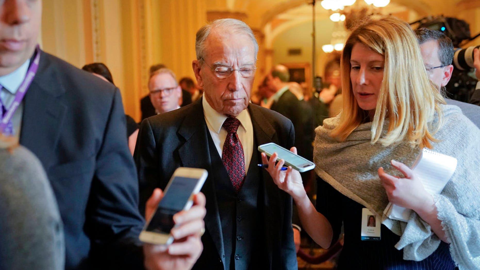 U.S. Sen. Chuck Grassley, R-Iowa, center, addresses reporters' questions on Capitol Hill in Washington.