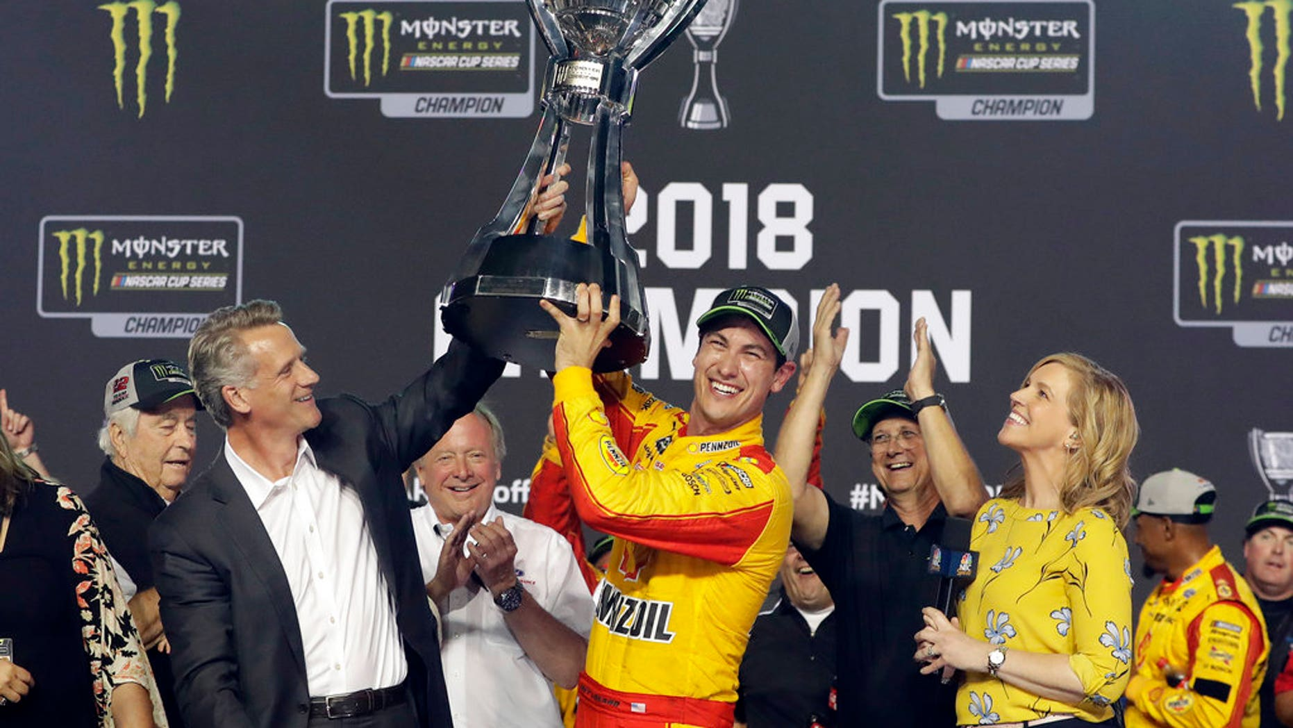 Joey Logano holds the trophy after winning the NASCAR Cup Series Championship auto race at the Homestead-Miami Speedway, Sunday, Nov. 18, 2018, in Homestead, Florida.