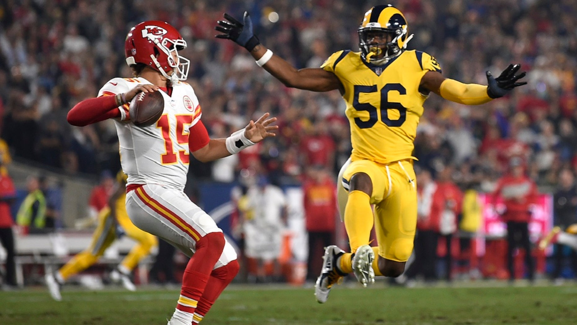 Kansas City Chiefs quarterback Patrick Mahomes, left, passes under pressure from Los Angeles Rams defensive end Dante Fowler (56) during the first half of an NFL football game Monday, Nov. 19, 2018, in Los Angeles.