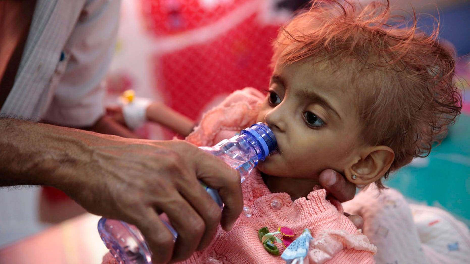 FILE: A father gives water to his malnourished daughter at a feeding center in a hospital in Hodeida, Yemen.