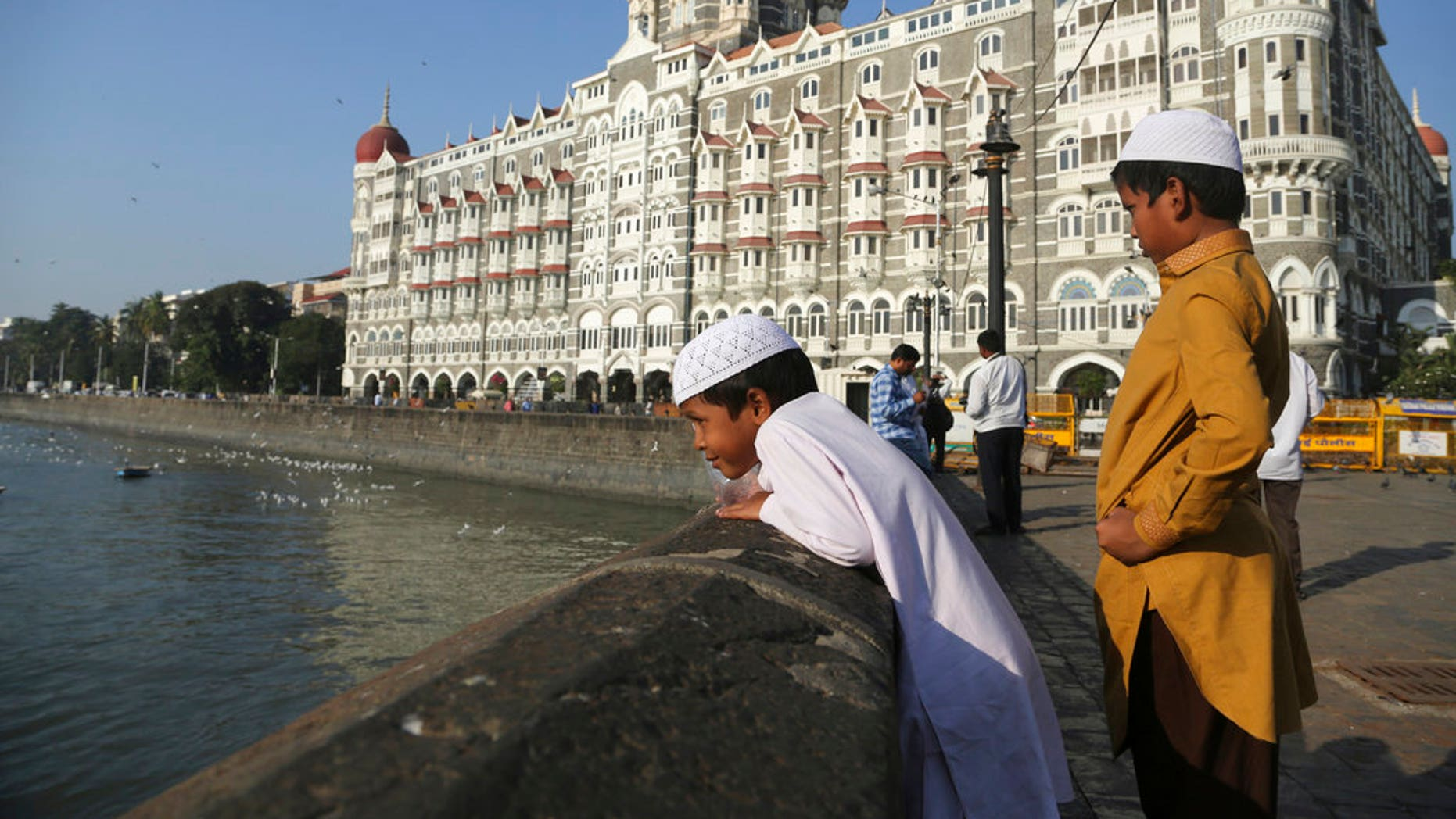 In this Nov 17, 2018, photo, two Muslim boys stand outside the iconic Taj Mahal Palace hotel, the epicenter of the 2008 terror attacks that killed 166 people in Mumbai, India.