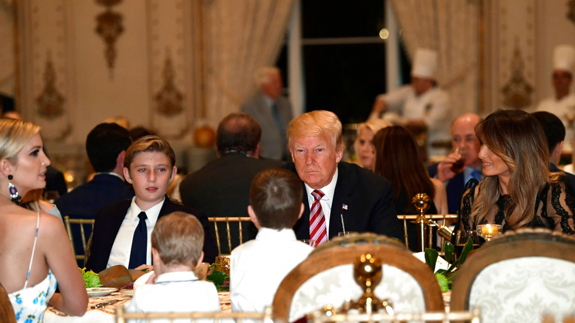 President Donald Trump, center, and first lady Melania Trump, right, sit with their family as they have Thanksgiving Day dinner at their Mar-a-Lago estate in Palm Beach, Fla., Thursday, Nov. 22, 2018. Ivanka Trump, left, and Barron Trump, second from left, attend.