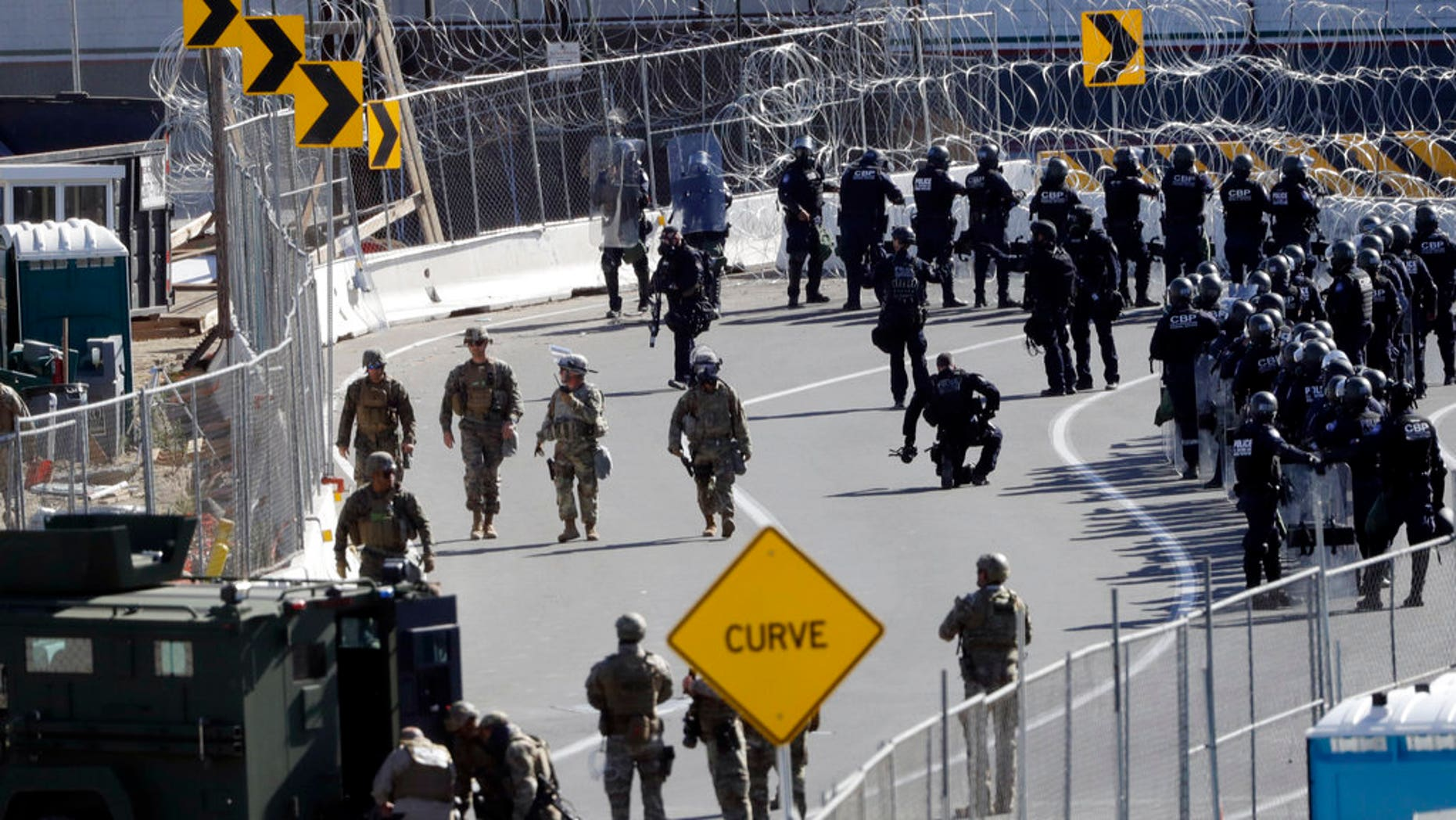 FILE: Military personnel and Customs and Border Protection officers gather along the southbound lanes of the San Ysidro port of entry in San Diego.