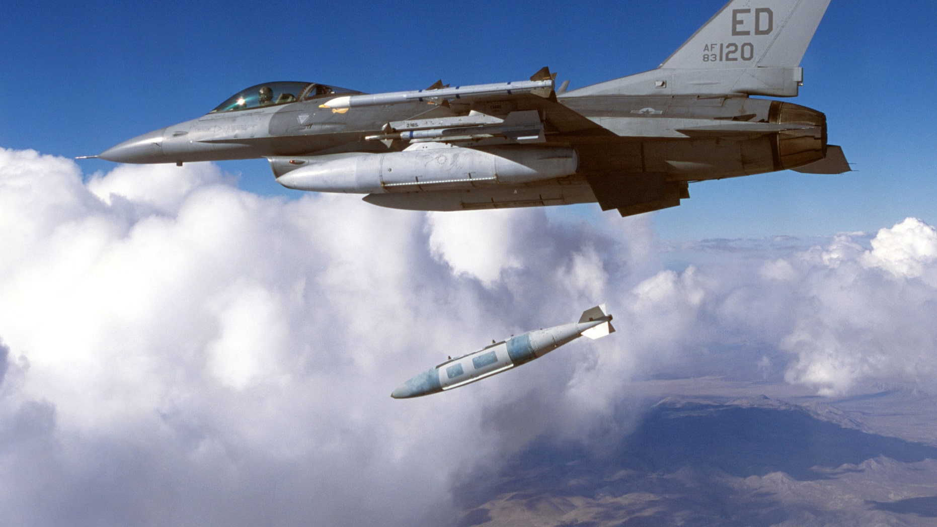 File photo - A Block 30 F-16 from the 416th Flight Test Squadron drops a Joint Direct Attack Munition (JDAM) during testing in January, 2003 at Edwards Air Force Base in California. (Photo by Tom Reynolds/U.S. Air Force/Getty Images)
