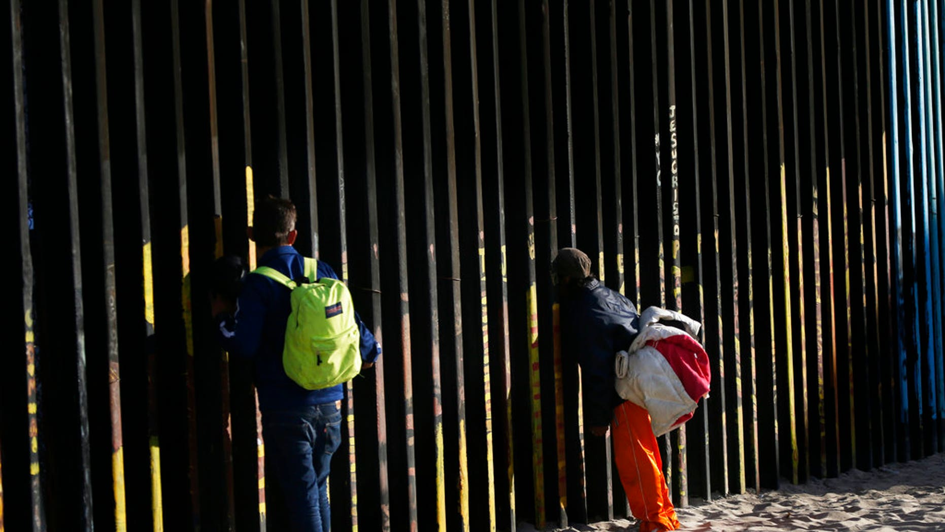 Central American migrants look through the border structure. (AP Photo/Marco Ugarte)